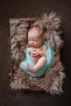 swaddled baby in box for newborn photography session