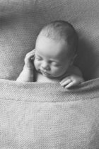 Newborn baby tucked into bed for studio baby photography pictures